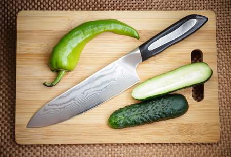 Knife kitchen with a blade of Damask steel on a chopping board Stock Photo