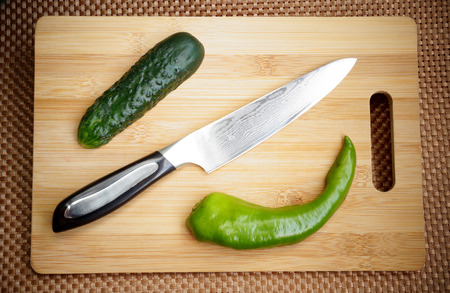 Knife kitchen with a blade from Damask steel on a chopping board