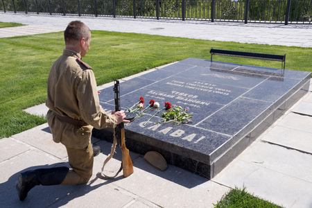 Fighter of Red Army bent a knelt at the grave of Marshal Chuikov on Mamayev Kurgan in Volgograd Stock Photo