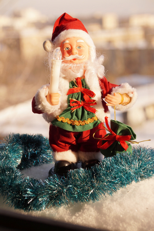 Toy Santa Claus in red clothes with a candle in a hand