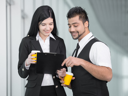 Confident businesswoman and businessman standing in office and drink coffee photo