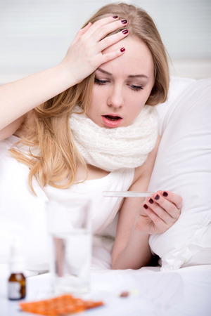Woman with thermometer sick colds, flu, fever and migraine in bed photo