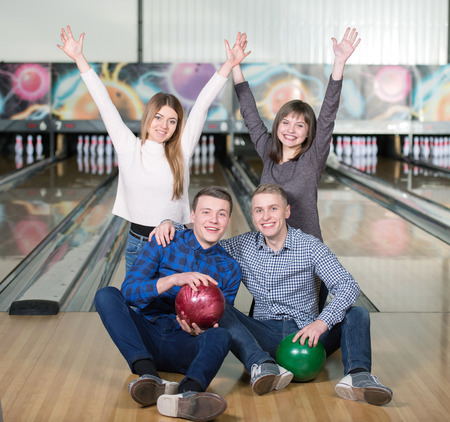 bowling alley: Funny young people smiling at the camera playing bowling Stock Photo