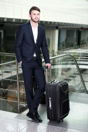 Young businessman with a suitcase and plane tickets at the\ airport to travel trips
