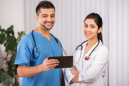 Two Indian doctors sitting working  together photo
