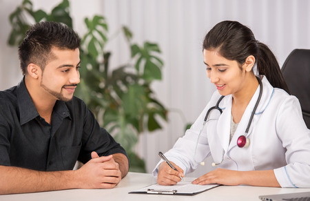 consulta m�dica: Mujer india m�dico comunicaci�n con los pacientes de sexo masculino