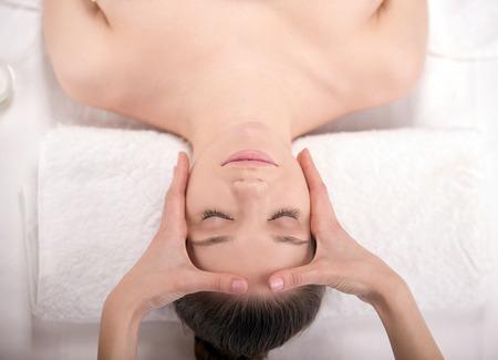 Beauty treatment. Top view of beautiful young women getiing facial massage photo