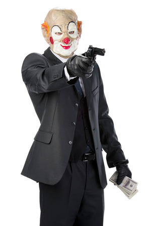 perpetrator: Gangster masked clown with a gun during a robbery isolated on white background Stock Photo