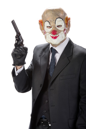 Gangster masked clown with a gun during a robbery isolated on white background photo