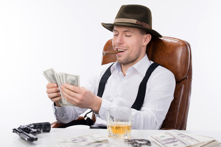 gangster sitting at a table counting money. on the table gun and brass knuckles photo