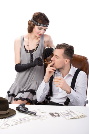 Male and female gangsters sitting at a table counting money. on the table gun and brass knuckles photo