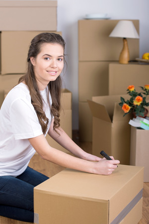 Writing on a carton box. Beautiful young woman marking a cardboard box and smiling at camera while more boxes laying on background photo