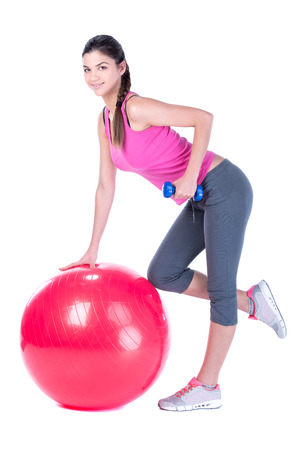 Young sport woman sitting on fitness ball with dumbells. Isolated on white . photo