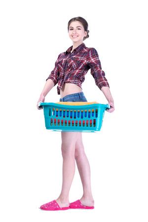 A smiling female holding a laundry basket. Isolated on white  photo