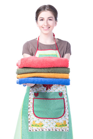 Bright picture of lovely housewife with towels. Isolated on white  photo