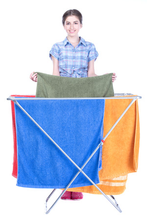 A smiling woman putting towels to dry. Isolated on white  photo