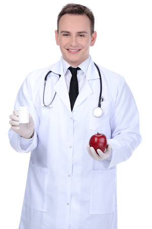 Confident medical doctor with tablets in one hand and apple in other isolated on white