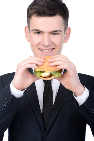 Young hungry businessman eating hamburger isolated on white background photo