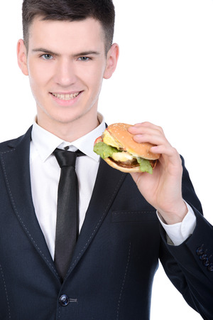 Young hungry businessman eating hamburger isolated on white background photo