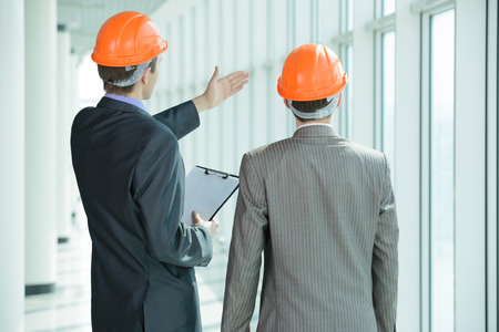 construction plans: Two men in hard hats at construction site