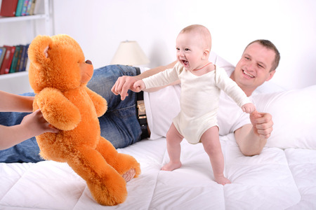 Parents play with newborn baby at home. Happy family. photo