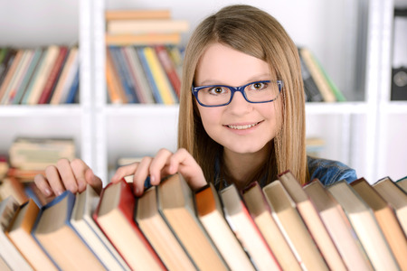 Young student girl with book selection bookshelf, school