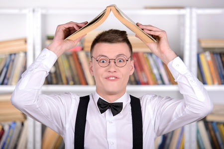 Smart young man intelehent in shirt and tie tie and glasses holding book on head standing in the library photo