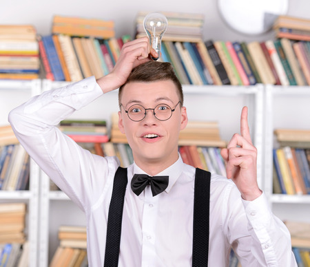 Smart young man intelehent in shirt and tie tie and glasses holding a light bulb while standing in a library photo