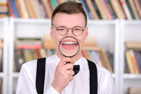 Smart young man intelehent in shirt and tie tie and glasses, standing holding a magnifying glass in a library photo