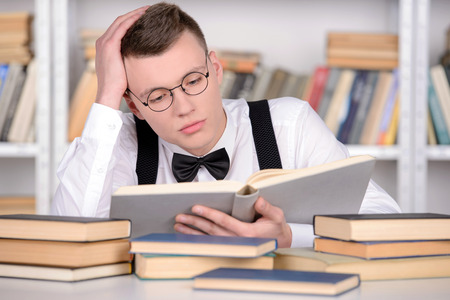 Smart young man intelehent in shirt and tie tie and glasses reading a book on the head while standing in a library photo