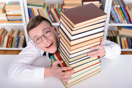 Smart young man intelehent in shirt and tie tie and glasses, standing holding many books in the library photo
