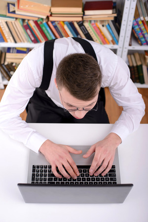 Computer nerd. Young man in shirt and bow tie typing something on computer and looking at camera with smile photo