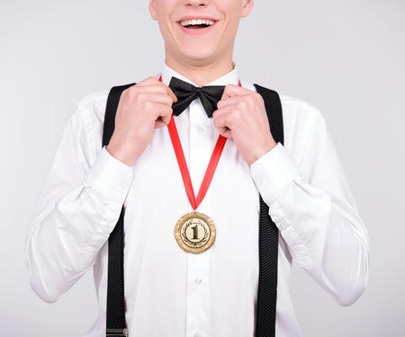 I am winner! Cheerful young man in bow tie and suspenders showing a gold medal to camera and smiling while standing against grey background photo