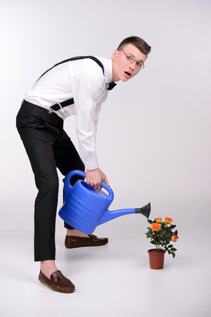 botanist: Young botanist. Young man in bow tie and suspenders watered a plant in his hands and smiling while standing against grey background Stock Photo