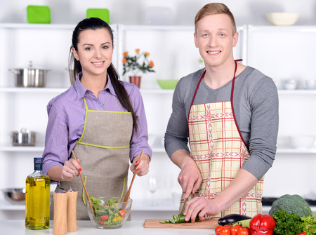 Cooking. Happy Couple Cooking Together - Man and Woman in their Kitchen at home Preparing Vegetable Salad. Diet. Dieting. Healthy Food photo