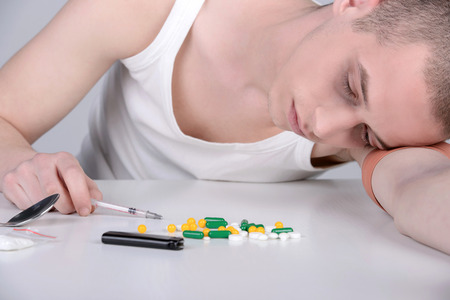 drug user: Portrait of a young drug user on a gray background
