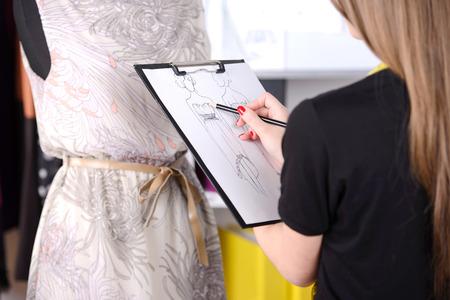 Couturier au travail. Enthousiaste jeune styliste dessin croquis et souriant