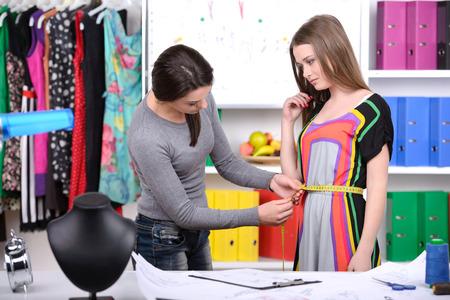 design studio: Fashion designers at work. Two cheerful young women working at fashion design studio
