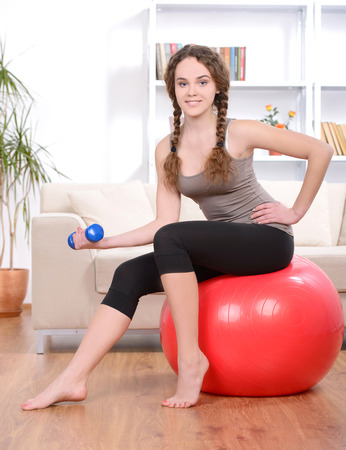 Portrait of young beautiful woman with a fitness ball at home photo