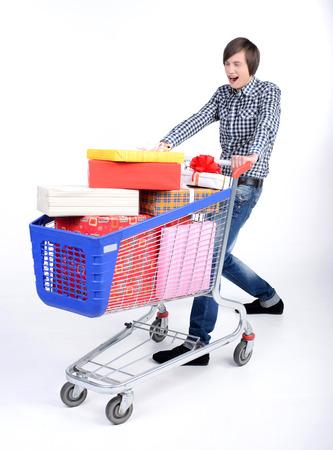 carretilla de mano: Joven corriendo y empujando un carrito de la compra de regalos aislados sobre fondo blanco