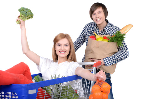 Supermarket. Happy couple with a shopping cart. Isolated over white background. photo