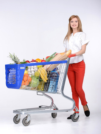 Portrait of a woman holding a shopping basket and shopping cart isolated on white background photo
