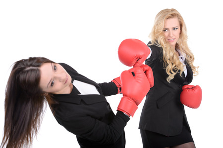 Two business women with boxing gloves fighting  isolated on white background  photo