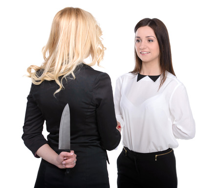 knifes: Dishonest partnership. Two young business woman shaking hands and holding knifes behind their backs.