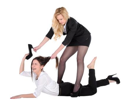 tienda de zapatos: Estos zapatos son los míos! Dos mujeres jóvenes enojados que luchan por los zapatos mientras aislados sobre fondo rosa