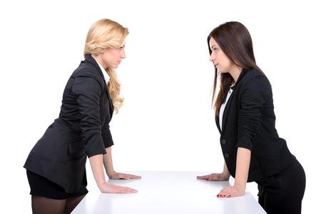 Femmes confrontation. Deux femmes en colère en regardant les uns les autres tout en tenant leurs mains sur la table Banque d'images - 28046907