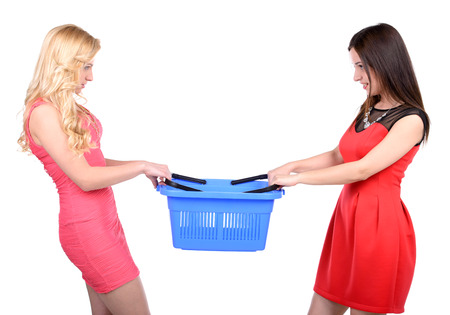 Two angry young women trying to take away one shopping basket while isolated on white background photo