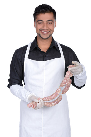 Happy cook holding sausage and smiling. young butcher demonstrating work in hands photo