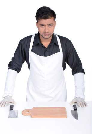 Man wearing apron holding knife. handsome butcher smiling and holding knife photo