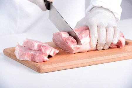 blade cut: Butcher cutting meat on chopping board, professional cook holding knife and cutting meat Stock Photo